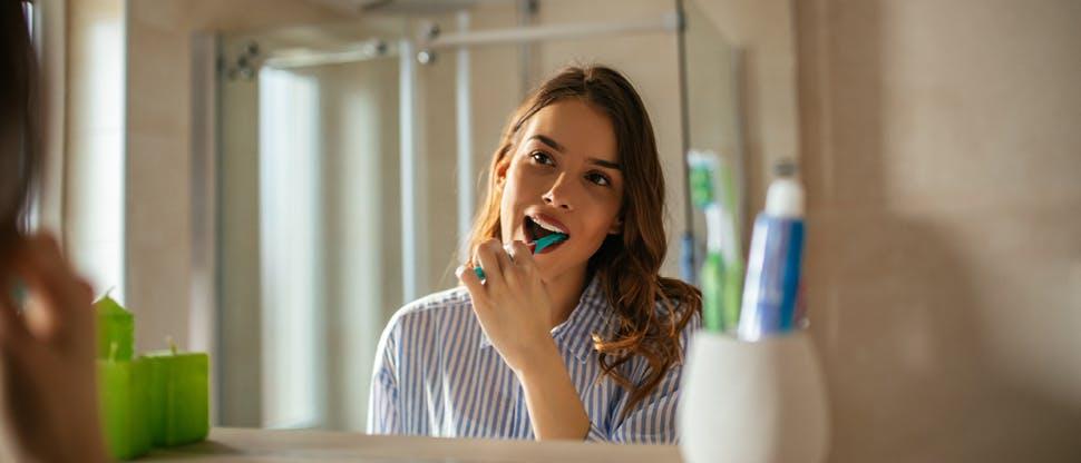 Pessoa escovando os dentes