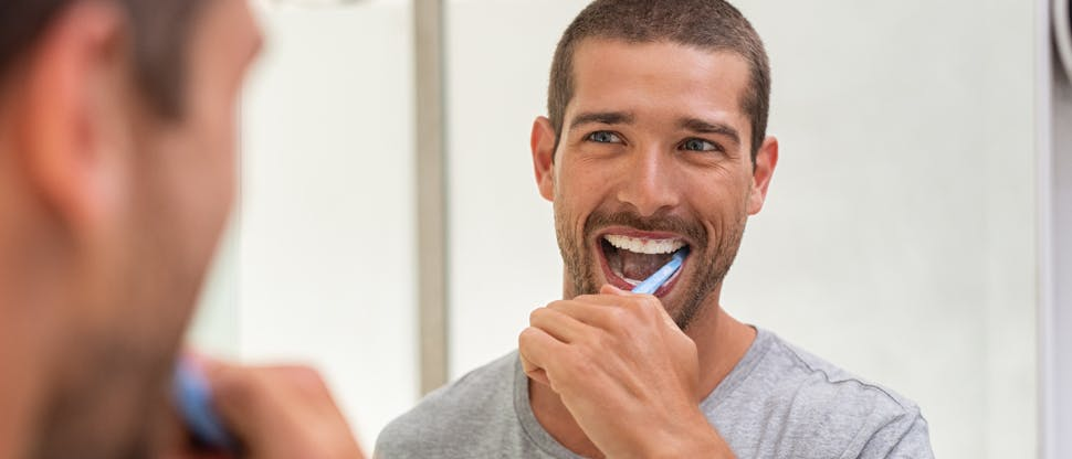 Homem escovando os dentes