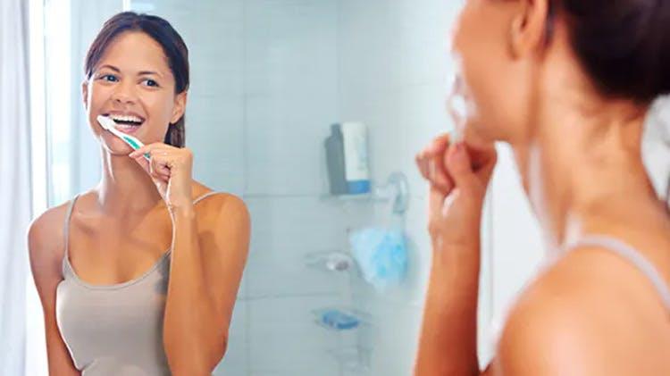 Femeie care îşi curăţă dinţii