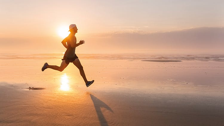 Bărbat alergând pe plajă