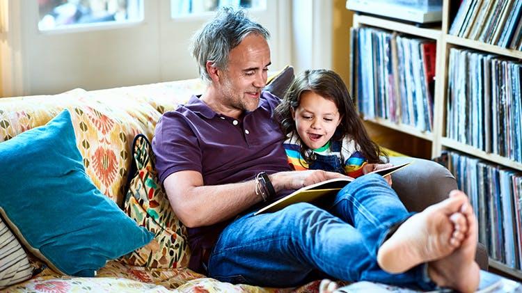 Bărbat citind alături de un copil