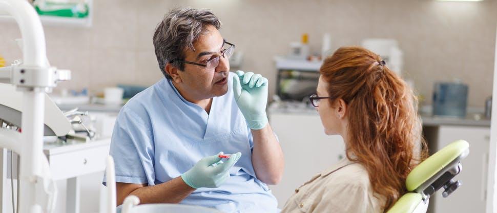 Pacient şi dentist, zâmbind fericiţi