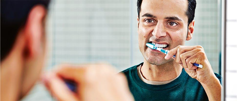 Bărbat care îşi periază dinţii