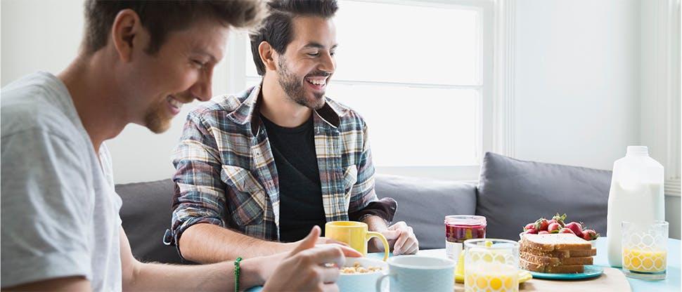 Doi bărbaţi care iau micul dejun