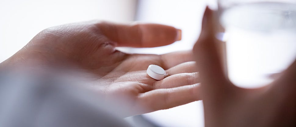 close-up-woman-holding-pill-in-hand-with-water