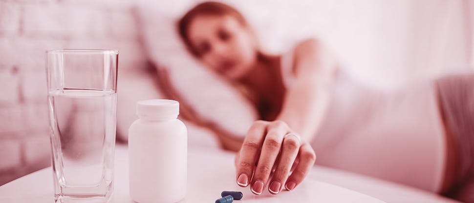 crop-ill-woman-taking-pills-in-bed