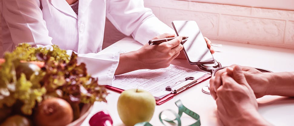 nutritionist-giving-consultation-to-patient-with-healthy-fruit-and-vegetable