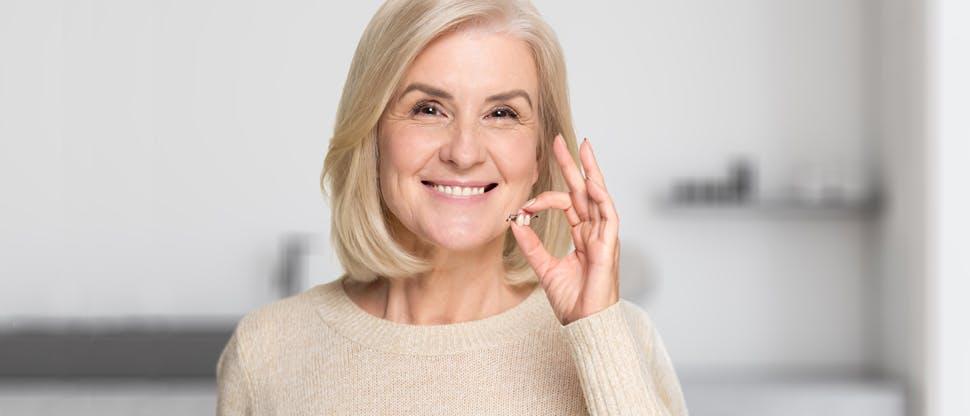 Женщина, показывающая частичный зубной протез