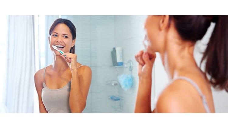 Женщина во время чистки зубов