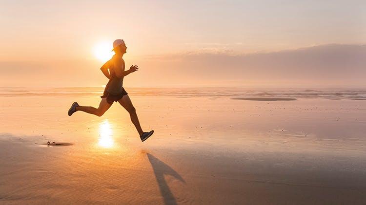 Мужчина, бегущий по пляжу