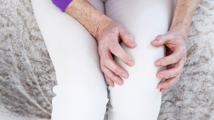 Женщина, сжимающая колено