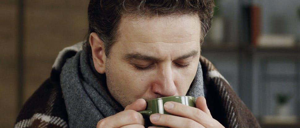 мужчина пьет напиток из чашки