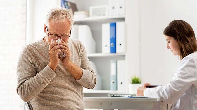 мужчина чихает на приеме у врача