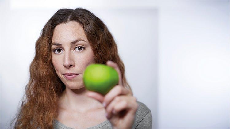 Жінка, що тримає яблуко