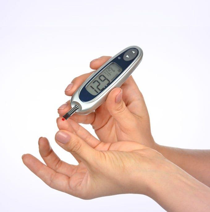Hand mit Blutzuckermessgerät