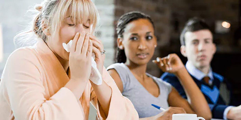 Woman sneezing around her friends