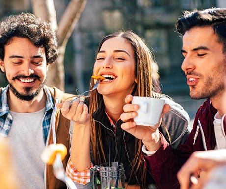 Um grupo de amigos se divertindo e fazendo um lanche à tarde.