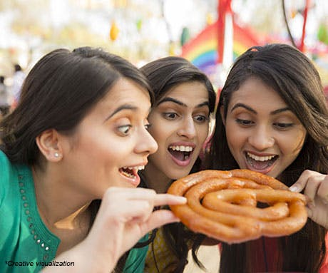Three girls eating a jalebi