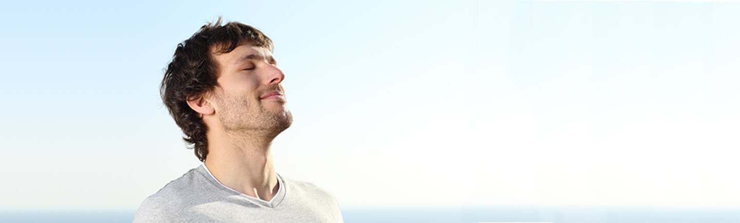 Young healthy man breathes freely probably after using a decongestant spray, which relieves conditions from cold to sinusitis and hay fever.