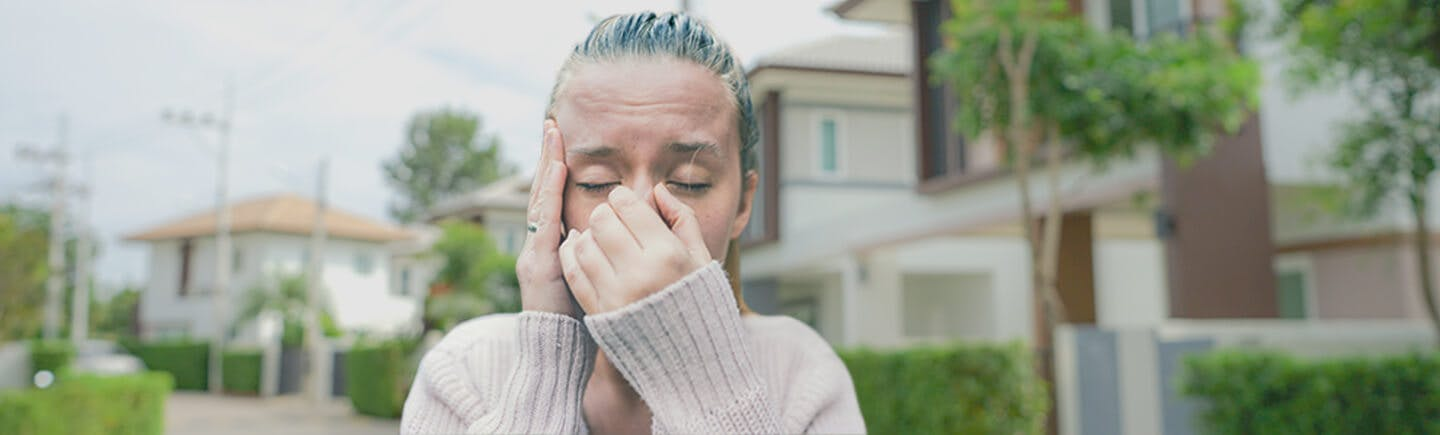 Young woman suffers from the effects of air pollution, which include irritated airways, congestion, exacerbated respiratory health conditions and irritated eyes.