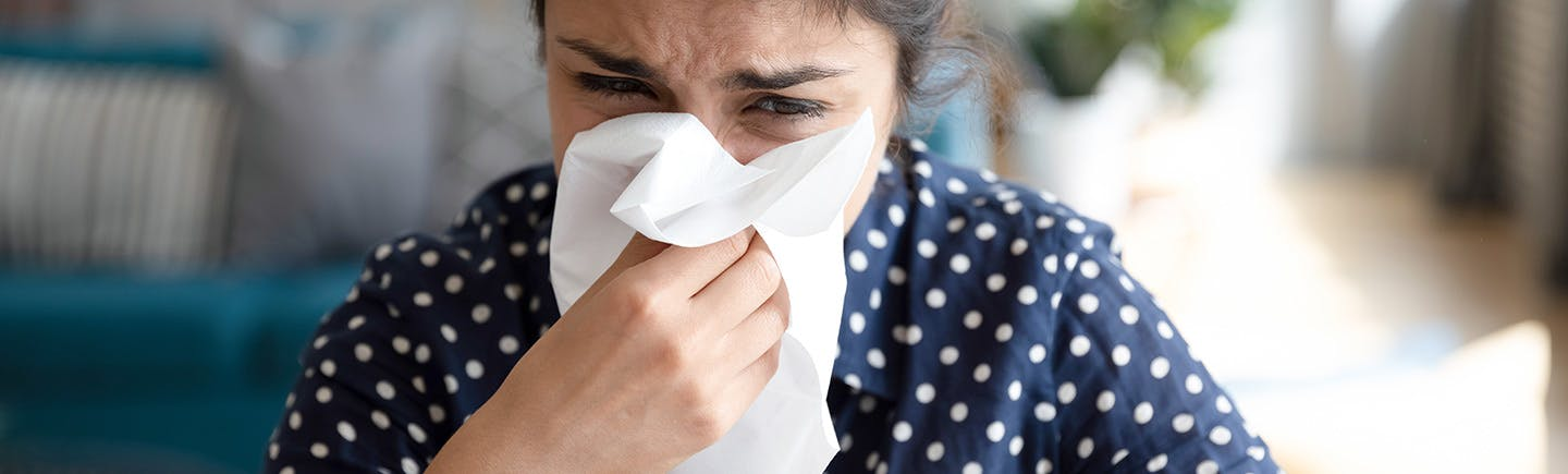 Mature Woman rubs her nose for persistent congestion symptoms.