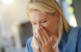 Middle-aged woman with allergy blowing her nose
