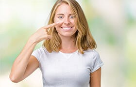 Young woman points to her nose, an organ  of the respiratory system that helps you breathe by filtering impurities from the air.