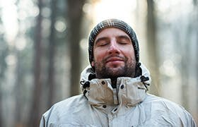 Young man in the middle of a forest breathes fresh air, as he is not exposed to air pollution.