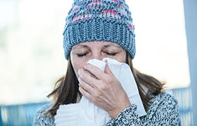 Mature woman with a cold and symptoms of congestion and blocked nose blows her nose into a tissue.