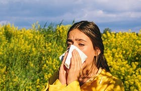 Woman sneezing due to hay fever allergy, which might be produced by pollen inhalation.