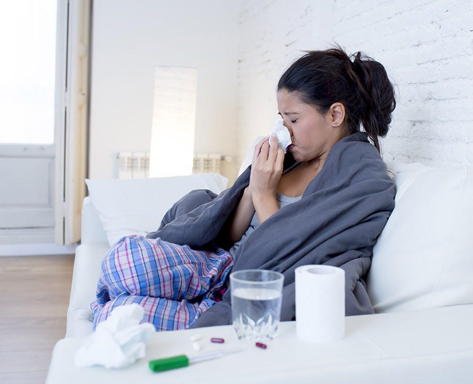 امرأة تعاني من السعال وألم في الجسم