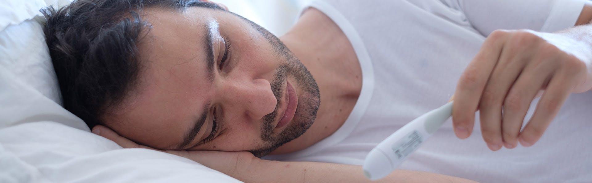 رجل في السرير يعاني من الحمى وارتفاع الحرارة