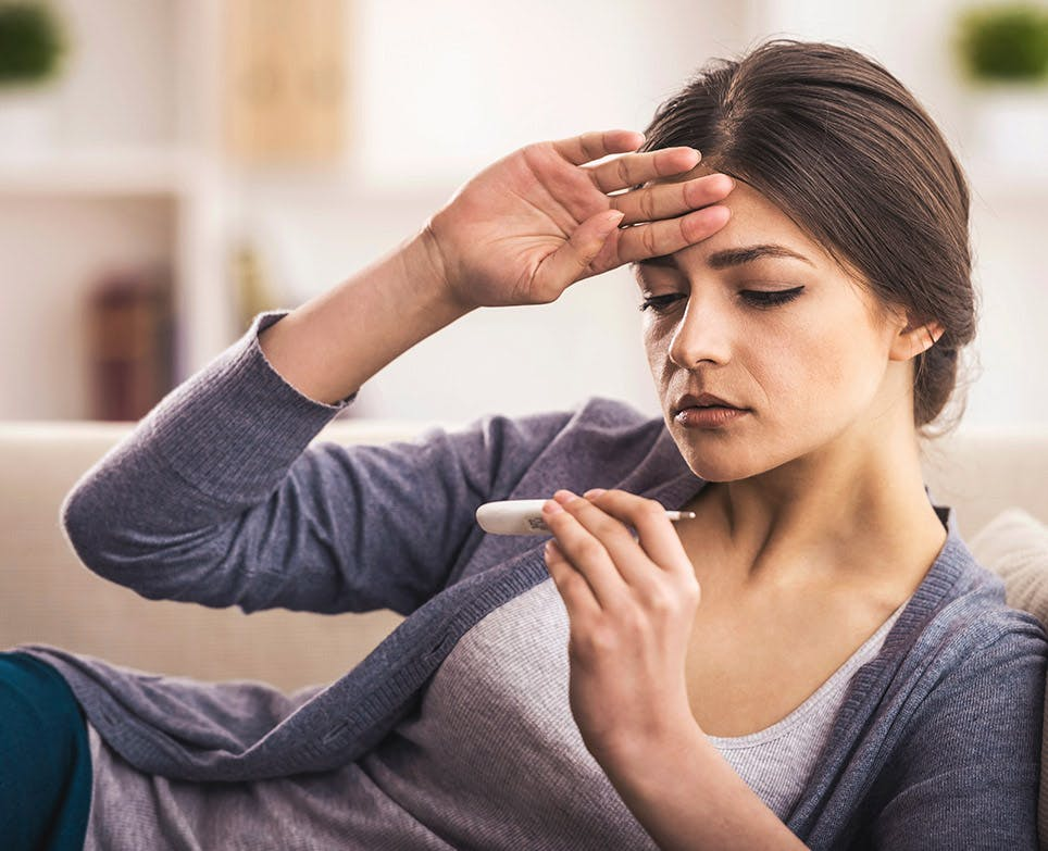 امرأة تعاني من الحمى وارتفاع الحرارة