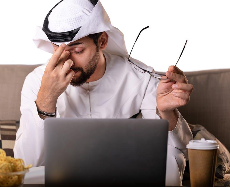 رجل ينزع نظاراته لأنه يعاني من صداع