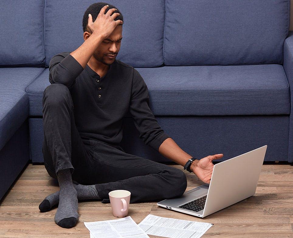 رجل يعمل على الكمبيوتر ويشعر بالصداع