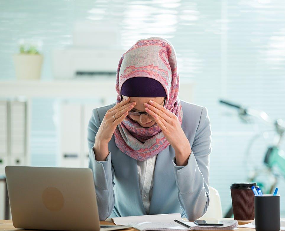 امرأة تعمل وتشعر بصداع شديد