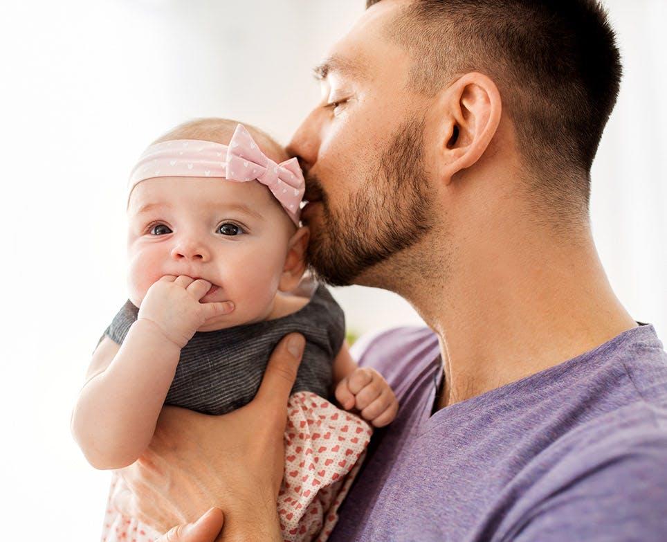 والد يقبّل طفلته