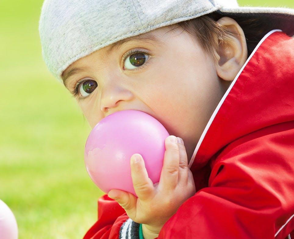 طفل يضع طابة في فمه