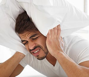 A man in bed suffering from an intense migraine