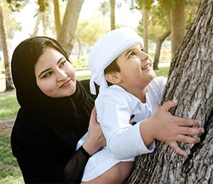 A mother holding her son as he climbs a tree