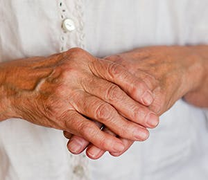 An old woman's right hand holding her left hand