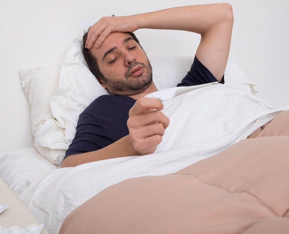 A man in bed reading an article about fever remedies
