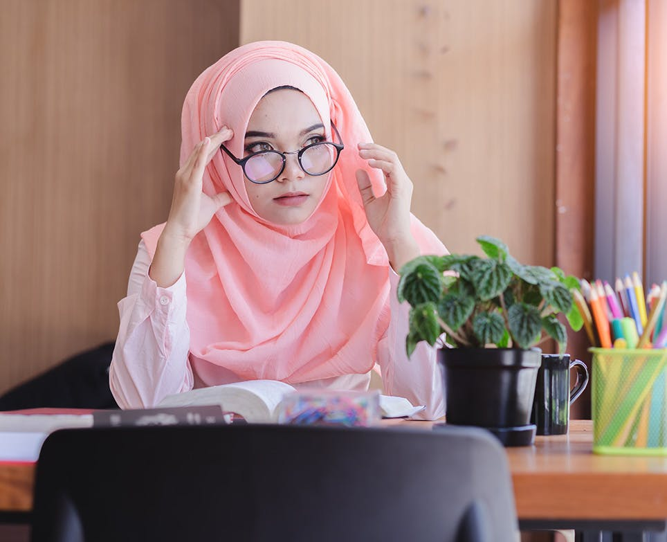 A woman wearing glasses and reading