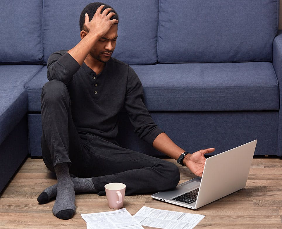 A man suffering from cluster headache while working on his computer