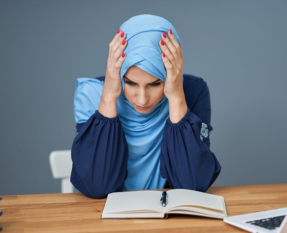 A woman reading and dealing with a headache