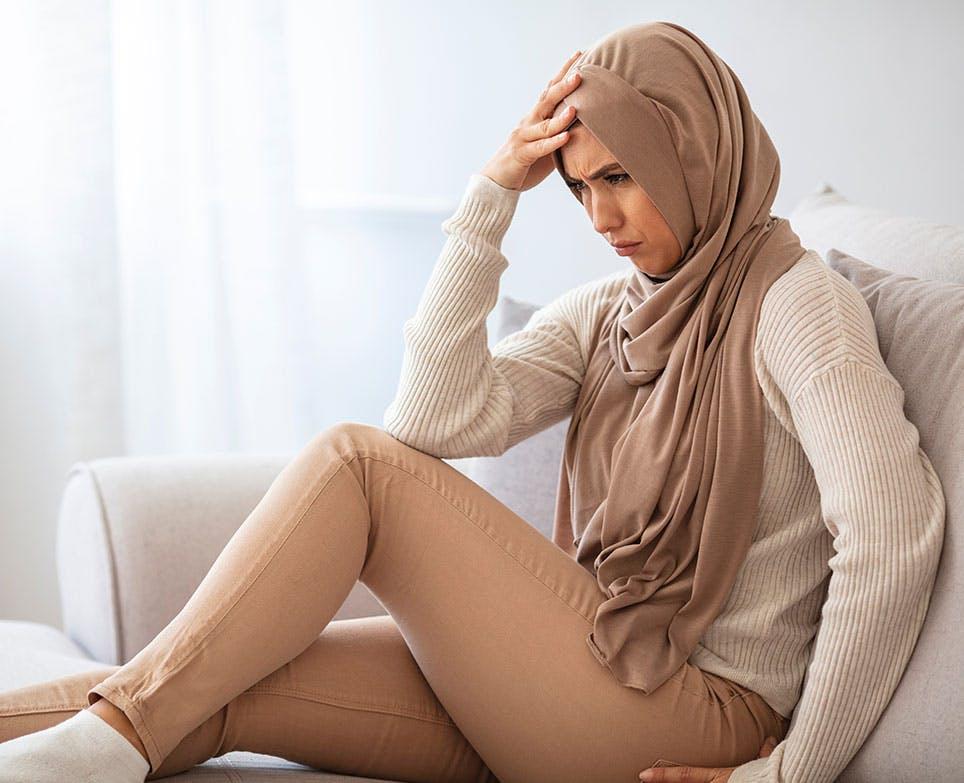 A woman at home dealing with a headache