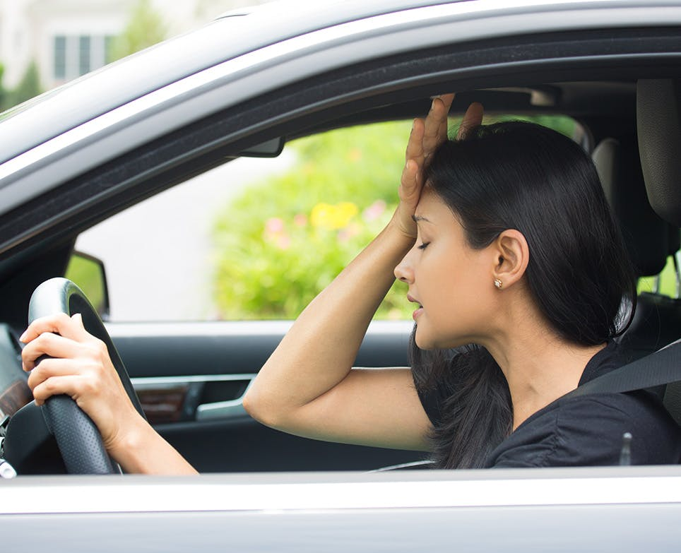 A woman driving and dealing with a headache