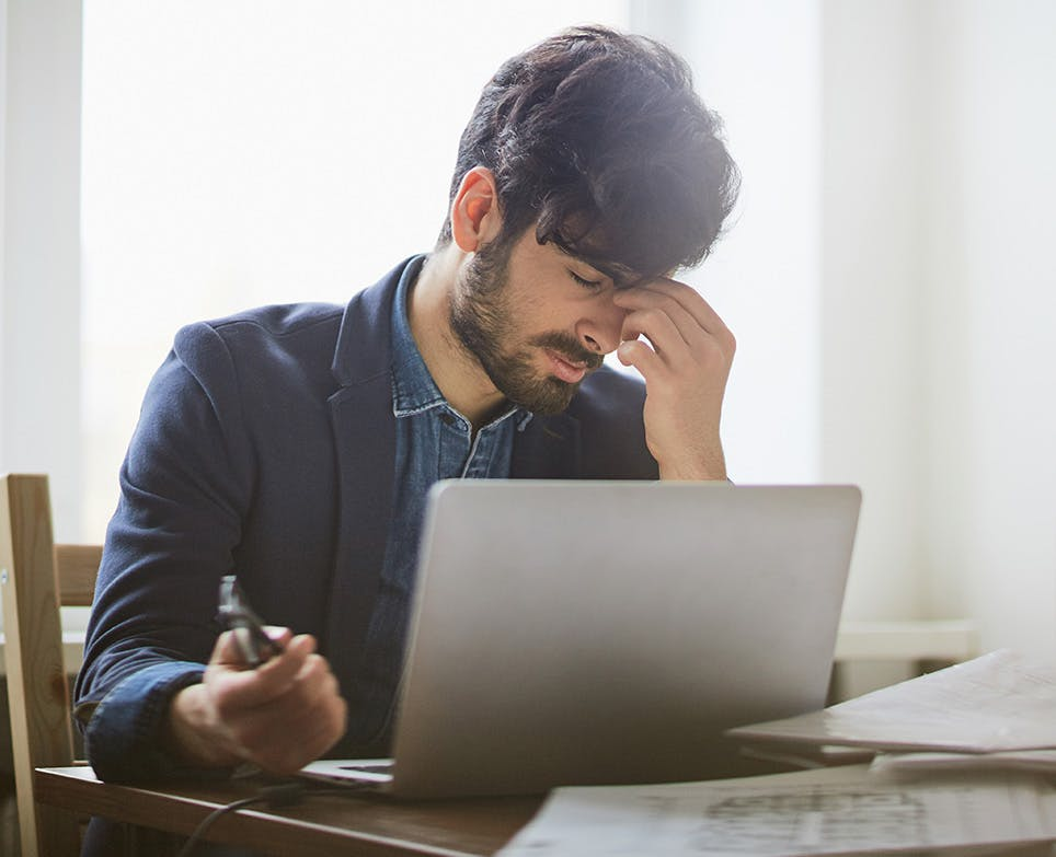 A man working on his computer while dealing with a migraine