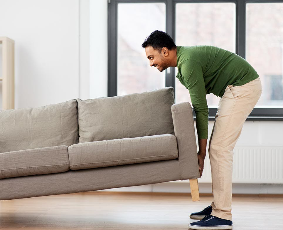 A man lifting a couch