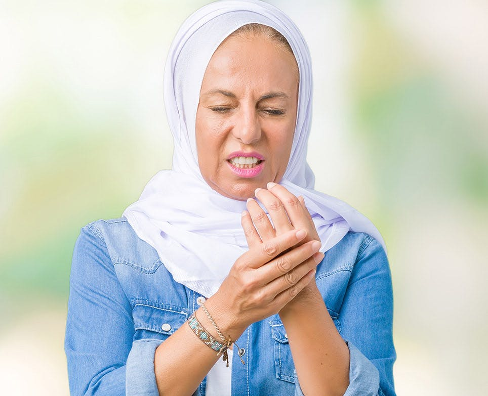 A woman experiencing bone pain in her hand